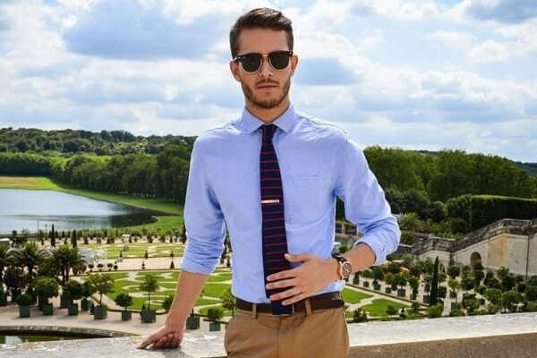 Men's khaki pants and blue shirt with striped tie for office look