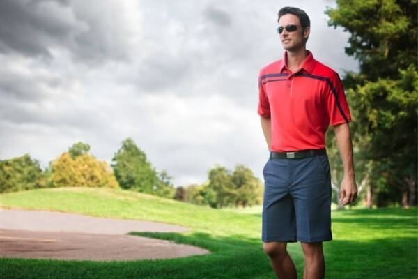 Men's red polo neck t-shirt with navy shorts for casual look