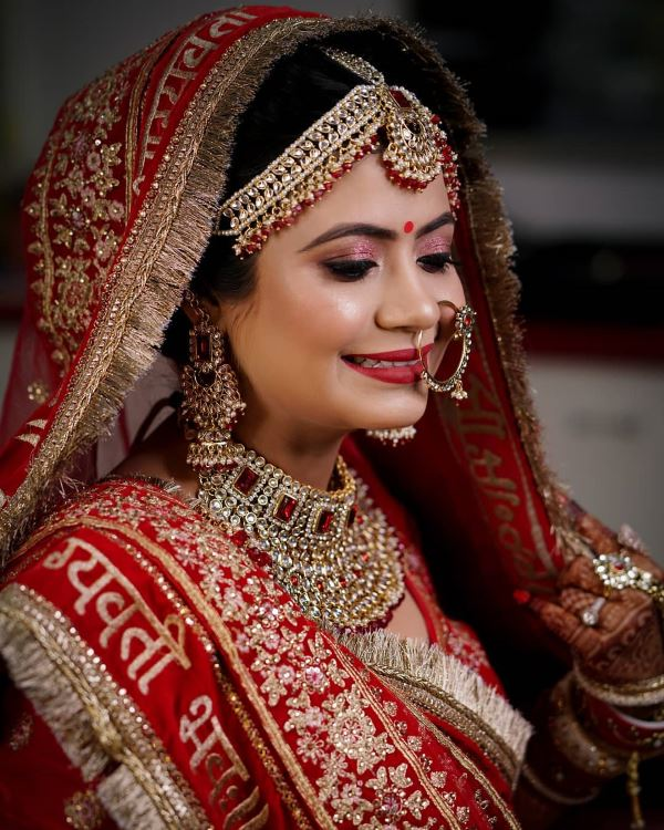 Glittery pink eyes with a bright red pout: Indian Bridal Makeup for Traditional Look