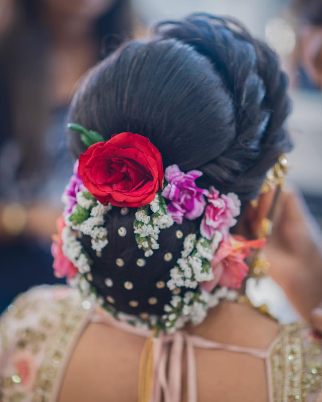 Multicoloured charm: Floral Bun Hairstyles for Brides this Wedding Season