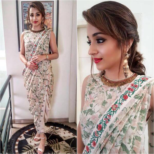 Trisha Krishnan is a film actress wearing a white dhoti style saree