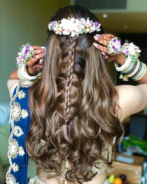 Bridal hairstyle for lehenga with loose beachy waves and floral pins