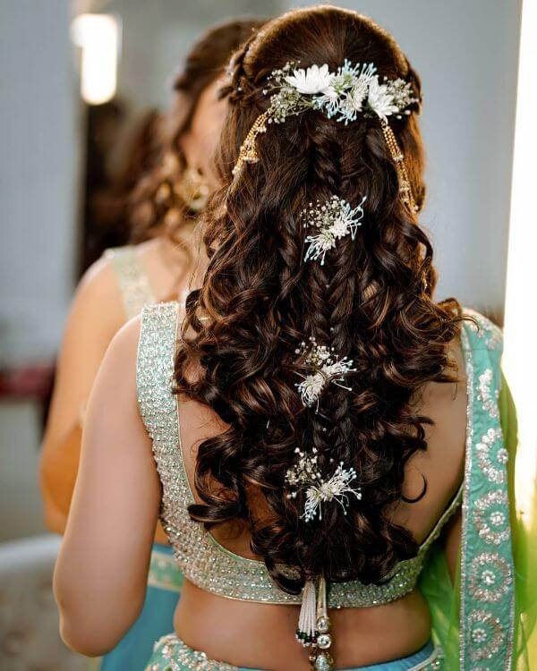Half braided and open hair both is involved giving a beautiful glamorous look with white hair accessories