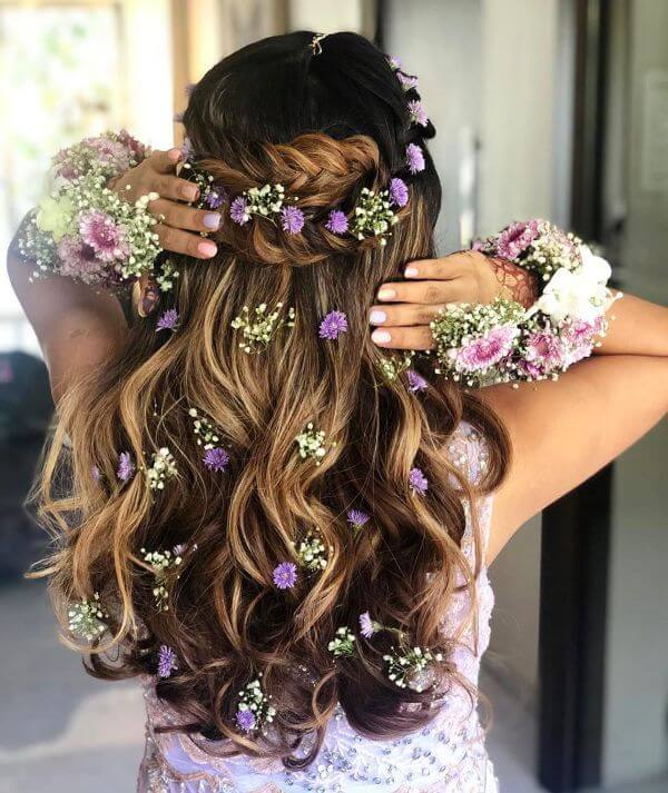 Braided crown with loose waves with a touch of purple flowers all over the hair