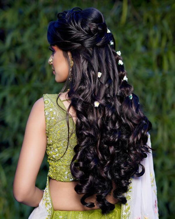 Twisted curls with loose braid on the top with white floral accessories
