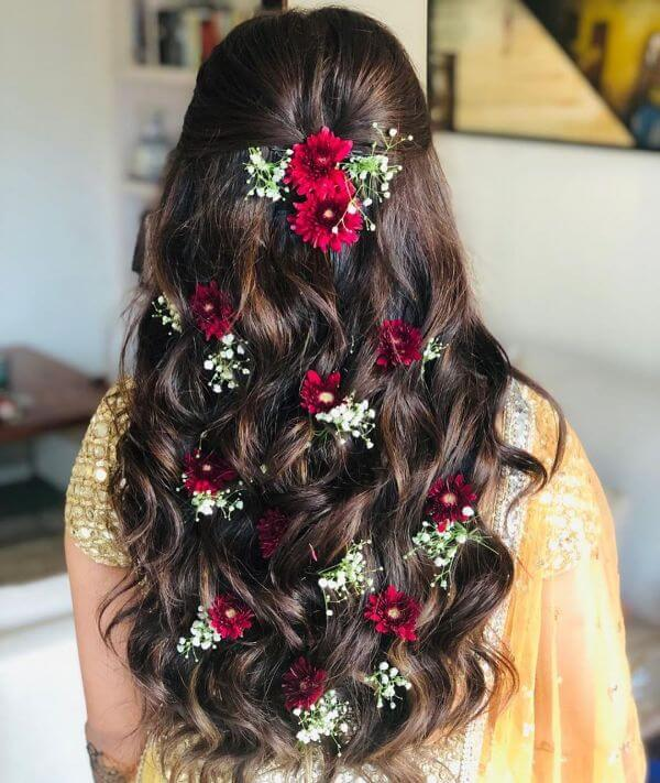 Half tucked wavy hair with floral accessories perfect for festive season