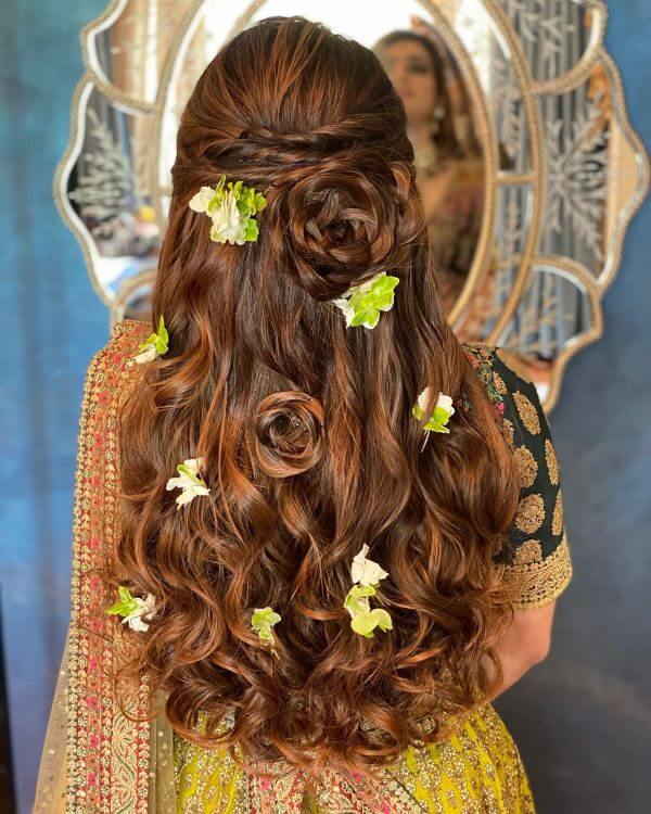 Rose bun and strands of baby's breath with loose curls