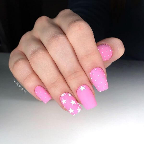 Pink nail art with stars painted on one nail with some dots on other