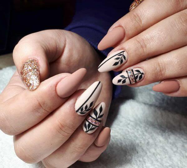 Painiting leaf with black on two nails with peach color and glitter effect nail art