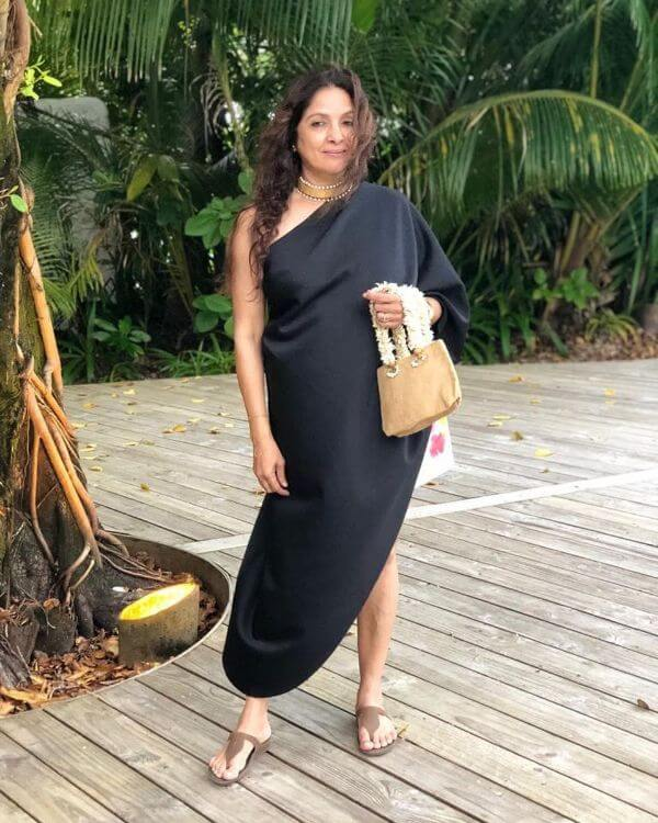 Neena gupta black long dress with brown small pouch for summer look