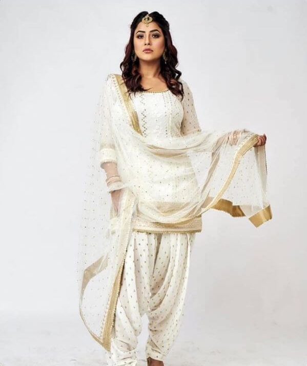 Shehnaaz Gill, an actress, model and singer wearing a white patiala suit with golden polka dots