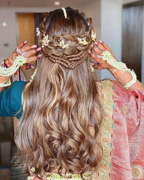 A picturesque soft curls half updo with accessories amidst the braid - Bridal Hairstyle Ideas for Haldi Function