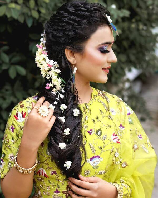 White flower tucked into the side braid hairstyle for festive season - Bridal Hairstyle Ideas for Haldi Function