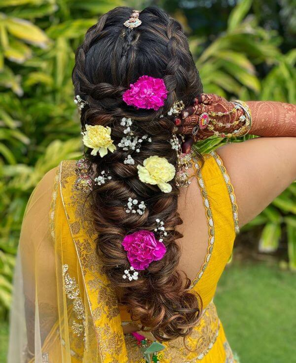Multiple messy braids with tiny multi-coloured flowers for hairstyle