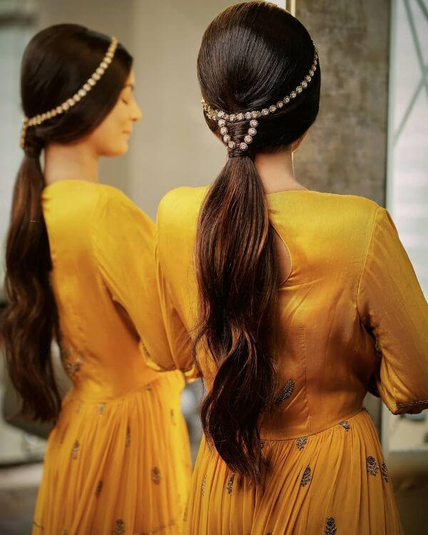 Low pony tail with hair accessory - Bridal Hairstyle Ideas for Haldi Function