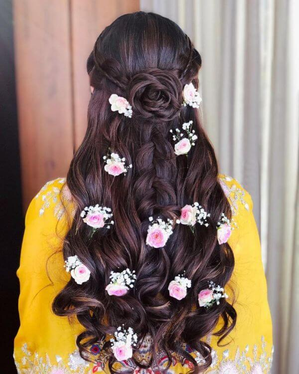 Braid the crown part of your hair and let the rest half of it flow in loose curls accessorise it with flowers or trinklets