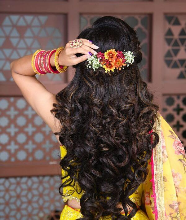 Heavy curled with a bunch of flowers in the centre of the head hairstyle for festive season