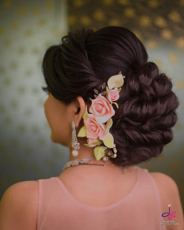 Multiple rolls messy bun with floral accessory for brides and bridesmaids