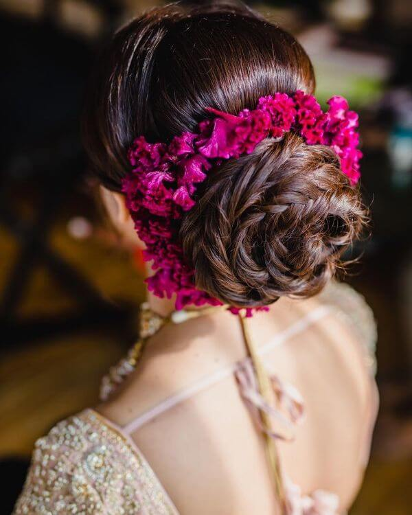 Rope twisted bun with pink floral accessories around for brides and bridesmaids