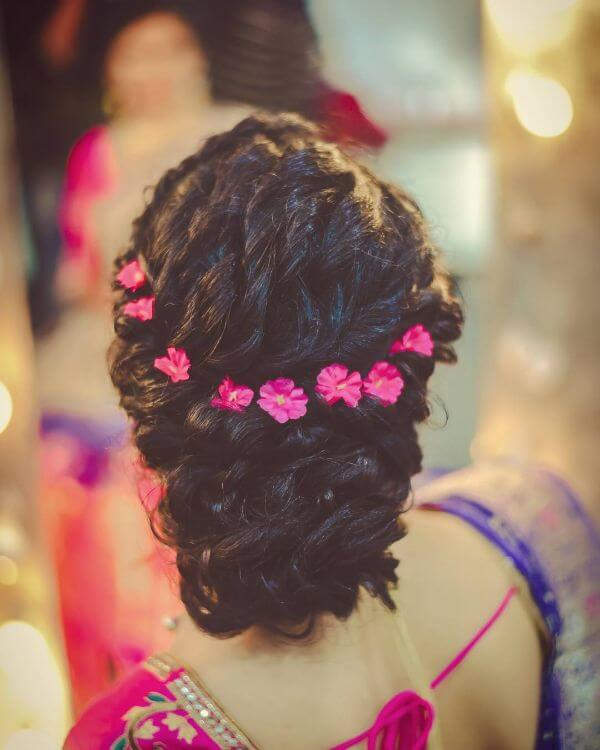 Ringlet bun hairstyle with pretty pink flowers for brides and bridesmaid