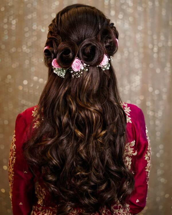 Rose hairdos with half up braided flower bun with soft curls Indian Bridal Hairstyles For Sangeet