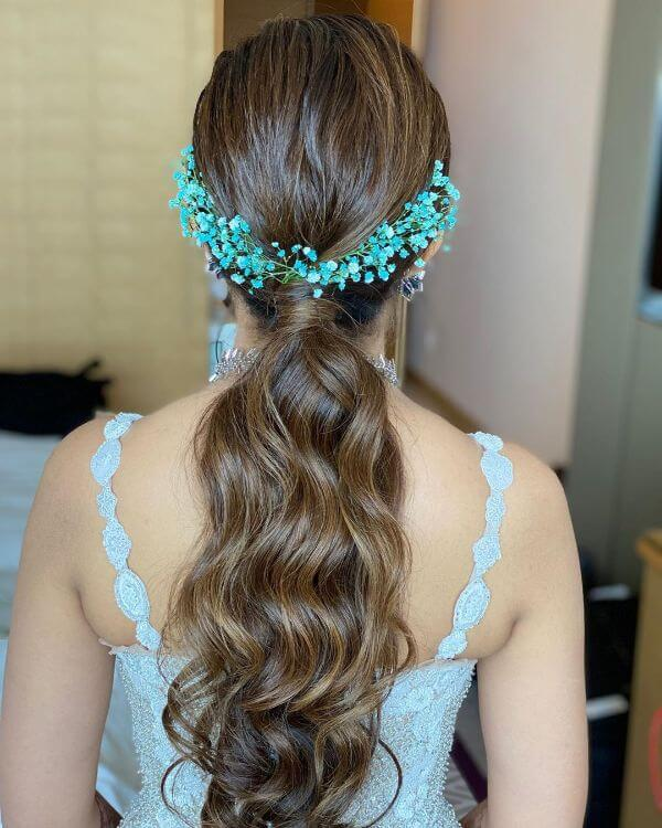 Low pony tail with loose wavy curls and blue flowers Indian Bridal Hairstyles For Sangeet