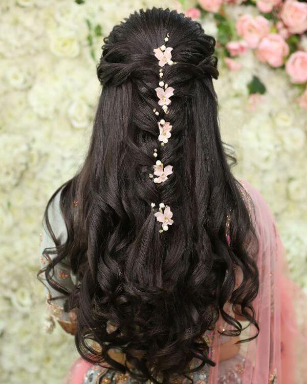 Gorgeous hairstyle with half hair braided and other half left to fall with curls in them with pink flowers in between
