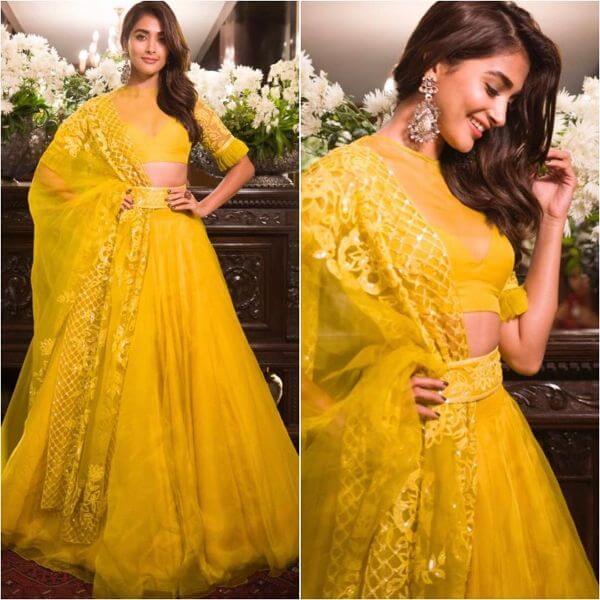 Pooja hegde's yellow half-sheer zero neck blouse with broad flared lehenga choli and dupatta