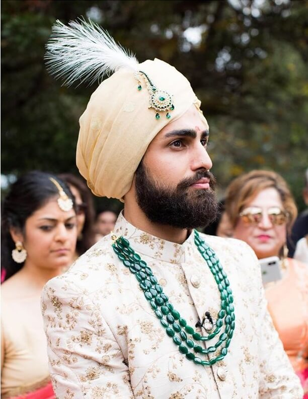 Green and yellow pleated Groom Kalgi Designs with white feather