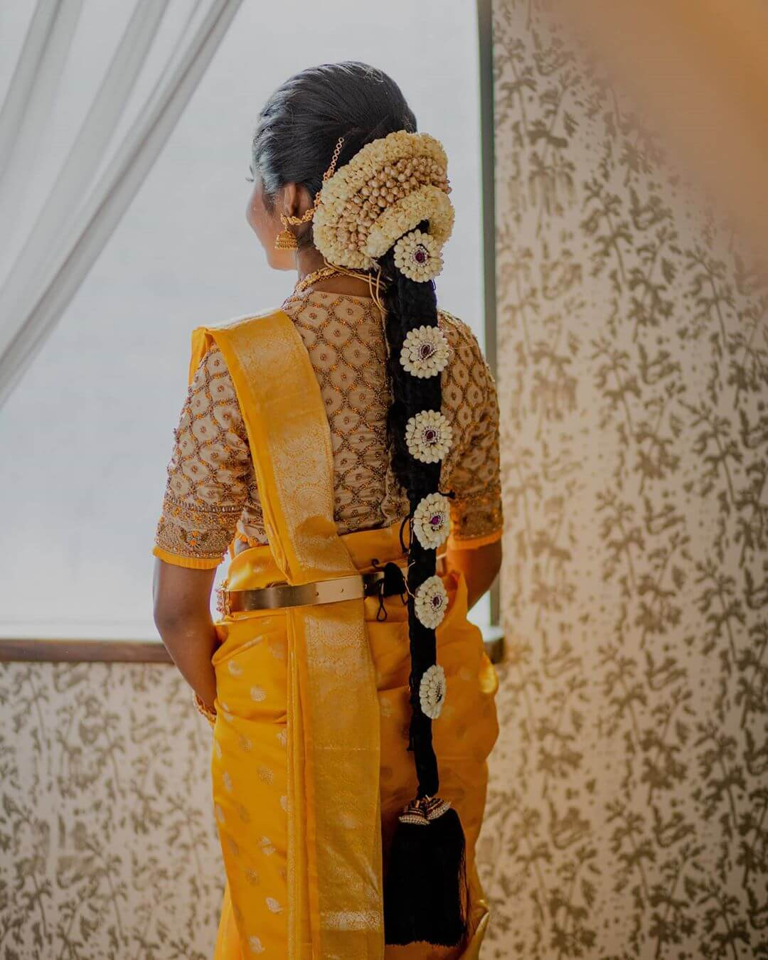 Traditional South Indian Bridal Hairstyle With Heavy Garland And Flower On Braid