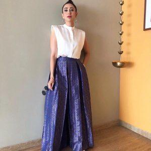 Karishma Kapoor has cut sleeves white shirt with a lower ban collar.